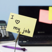 "Physician with ""I love my job"" note on desk"