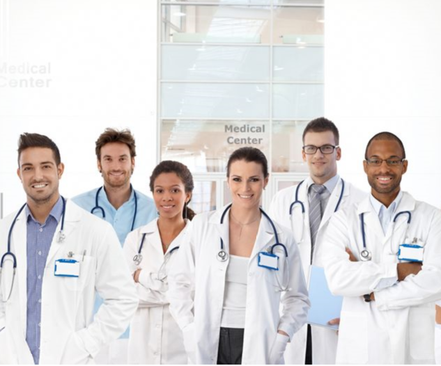 A team of doctors smiles at a group photo event.