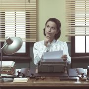 Vintage woman writes a letter of recommendation at a typewriter. The article offers 7 tips for writing a letter of recommendation