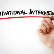 "A hand and marker write the text, ""motivational interviewing."" The article discusses how concepts of motivational interviewing can be incorporated and can benefit physician recruitment"
