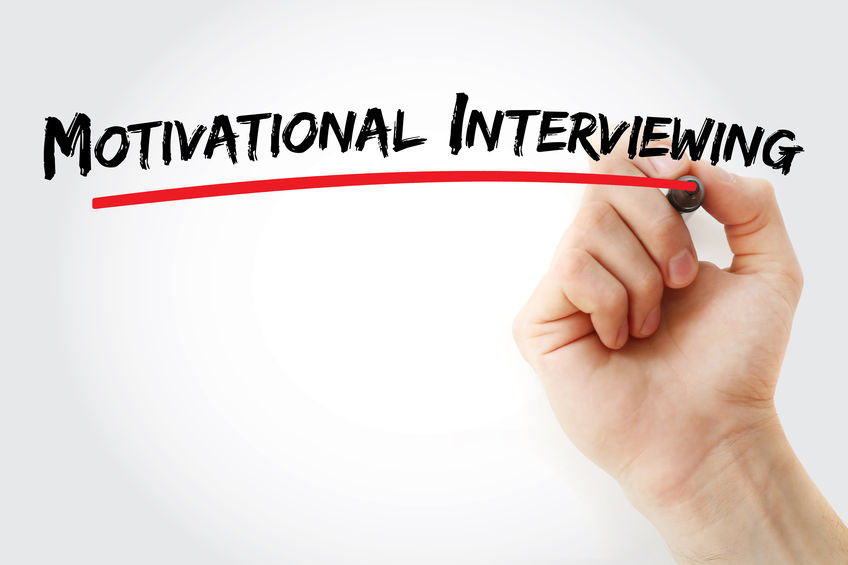 """A hand and marker write the text, """"motivational interviewing."""" The article discusses how concepts of motivational interviewing can be incorporated and can benefit physician recruitment"""