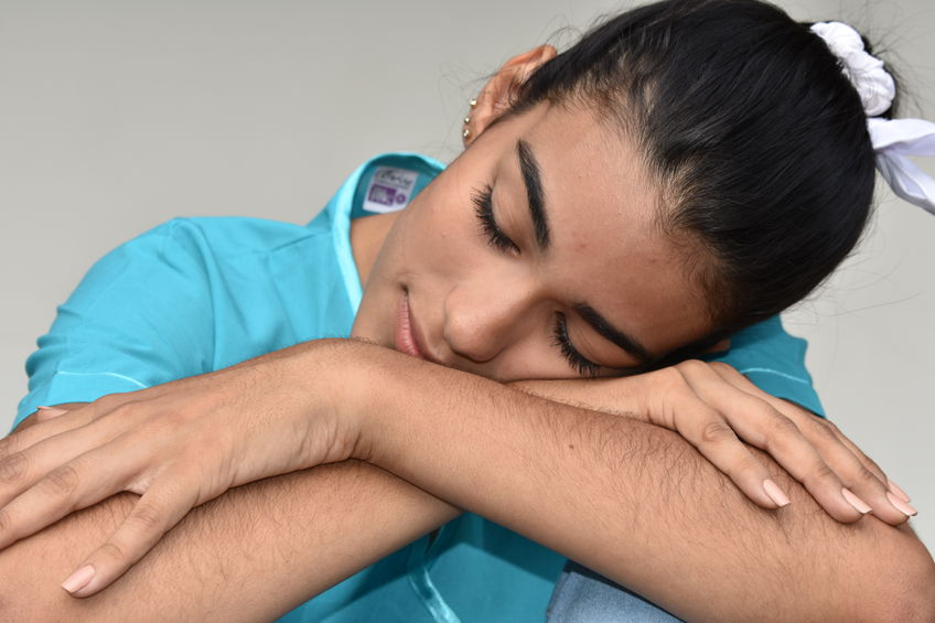 A sleepy female nurse or physician is resting her head on her arms