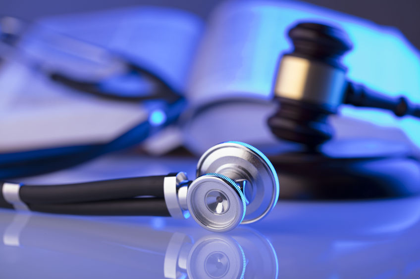 Medical law concept. A judge's gavel next to a stethoscope and a medical text book.