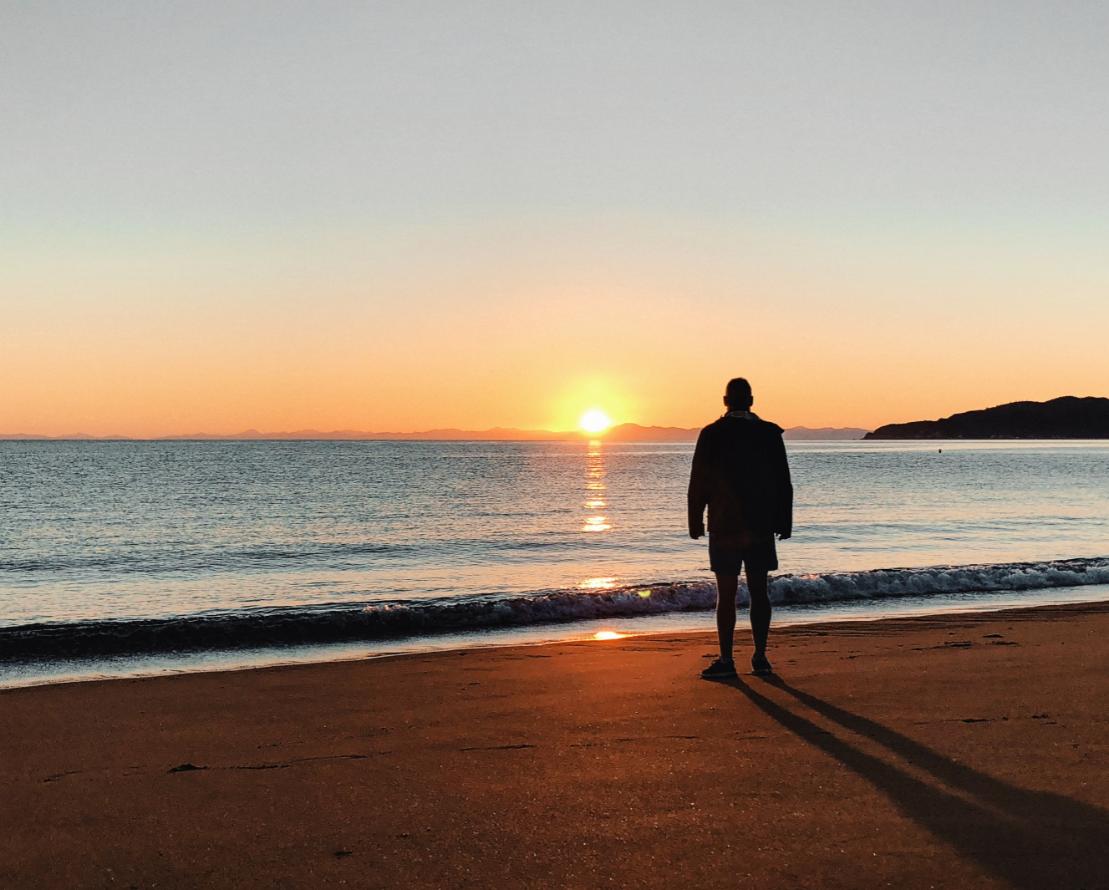 Man overlooking sunset on the ocean