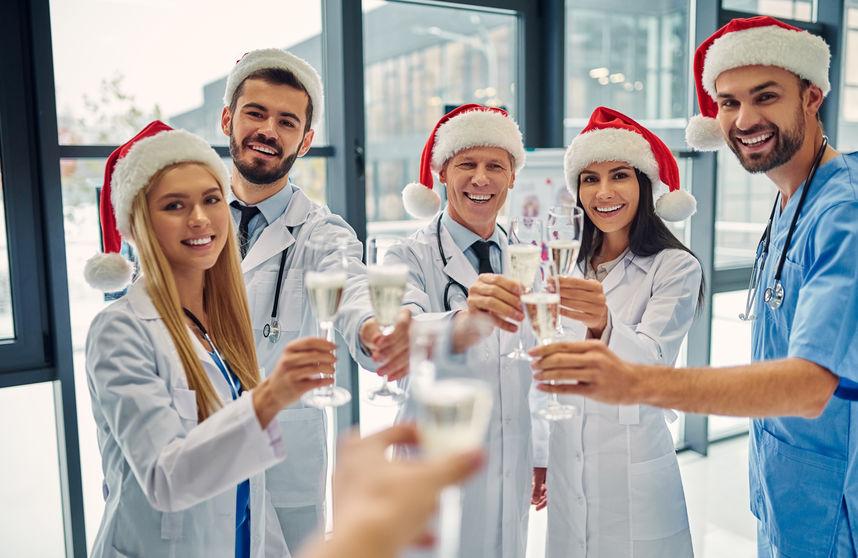 Doctors in santa hats clink champagne