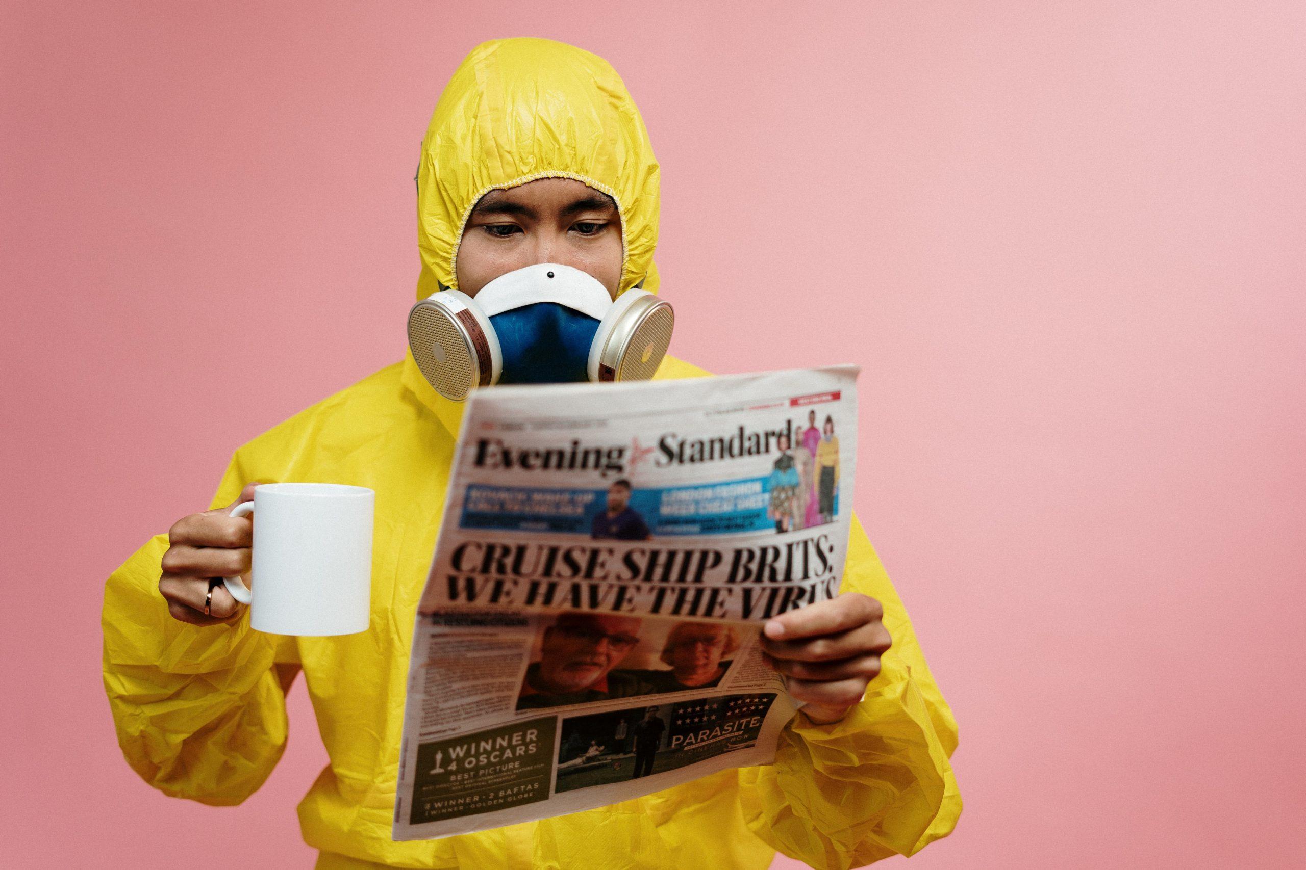 A man in a hazmat suit reads the paper