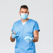 A man in blue scrubs reaches out with PPE masks